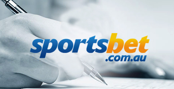 Hand hovering a pen above a piece of paper behind Sportsbet logo
