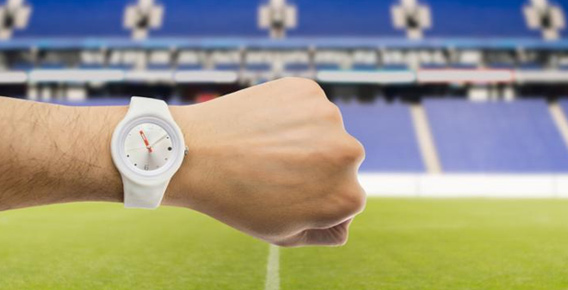 Man with wrist turned to show watch time in front of empty stadium stand